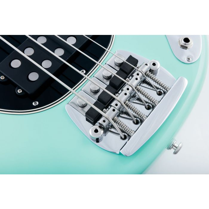 Closeup view of the vintage-style bridge on a Music Man Old Smoothie bass with a Mint Green finish