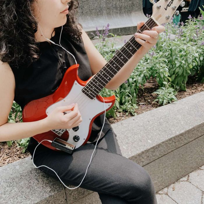 Woman Playing Vox SDC-1 In The Street with an AmPlug Headphone Guitar Amplifier
