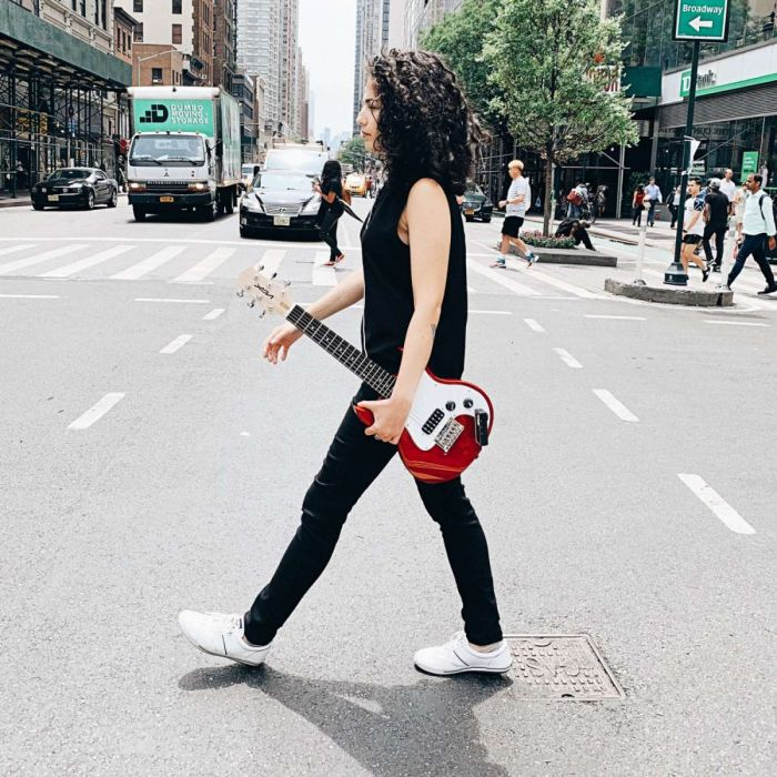 Woman Crossing The Street with Vox SDC-1 Mini Electric Guitar Under Her Arm