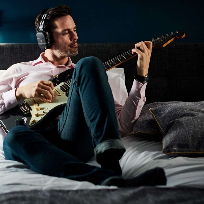 Man Playing Boss Waza-Air Headphones On A Bed