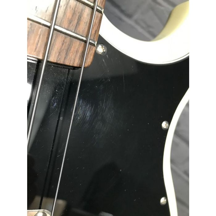 Closeup of the pickguard on a Pre-Loved Yamaha BB2025X 5-String Bass, Vintage White